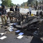 Pakistani police officers examine the site of an explosion in Quetta, Pakistan, Friday, June 23, 2017. A powerful bomb went off near the office of the provincial police chief in southwest Pakistan on Friday, causing casualties, police said. (AP Photo/Arshad Butt)